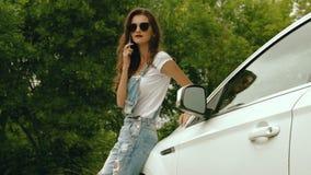 Signora alla moda in vetri che stanno l'automobile vicina ed ha detto dal telefono video d archivio