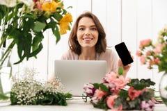 Signora allegra del fiorista che sta con i fiori che mostrano esposizione del telefono cellulare Immagini Stock