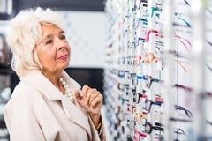 Signora anziana al deposito di vetro fotografie stock
