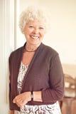 Signora anziana allegra a casa che sta Fotografia Stock