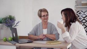 Signora anziana che fa le note e che spende tempo con la figlia adulta archivi video
