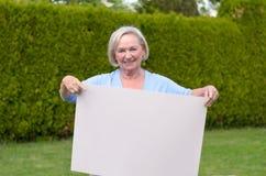Signora anziana che mostra una lavagna in bianco Fotografia Stock Libera da Diritti