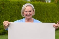 Signora anziana che mostra una lavagna in bianco Fotografia Stock