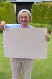 Signora anziana che mostra una lavagna in bianco Immagini Stock