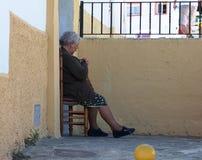Signora anziana che riposa sulla sedia fuori della sua casa a Ronda fotografie stock