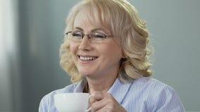 Signora anziana che si siede sul sofà, prendente la tazza di tè che gode dell'odore, si rilassa a casa stock footage