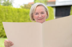 Signora anziana che tiene una carta in bianco Fotografia Stock