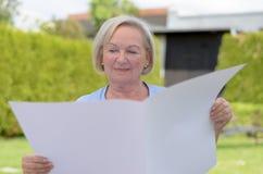 Signora anziana che tiene una carta in bianco Immagine Stock Libera da Diritti