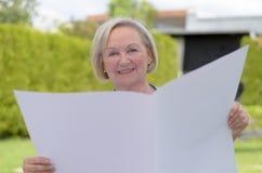 Signora anziana che tiene una carta in bianco Fotografia Stock Libera da Diritti