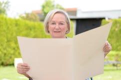 Signora anziana che tiene una carta in bianco Fotografie Stock