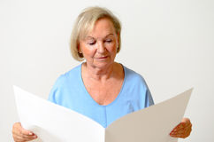 Signora anziana che tiene una carta in bianco Immagini Stock Libere da Diritti