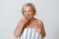 Signora anziana che usando spazzola interdental Fotografia Stock