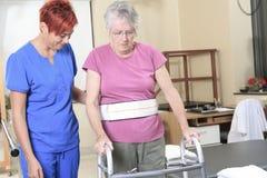 Signora anziana con il suo fisioterapista in a immagini stock
