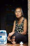signora anziana del lao che si siede alla sua porta che mastica noce di betel fotografia stock