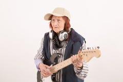 Signora anziana divertente che gioca chitarra elettrica fotografie stock