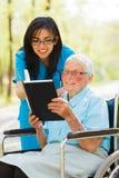 Signora anziana nella lettura della sedia a rotelle fotografia stock