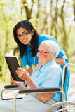 Signora anziana nella lettura della sedia a rotelle immagini stock libere da diritti