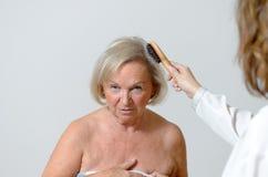 Signora anziana ottiene lei i capelli pettinati Fotografie Stock
