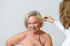 Signora anziana ottiene lei i capelli pettinati Fotografia Stock