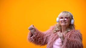 Signora anziana positiva in cappotto rosa ed occhiali da sole rotondi che ascolta la musica immagine stock