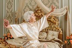 Signora anziana serena che sveglia nella mattina Immagine Stock