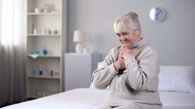 Signora anziana sorridente che si siede da solo ed abbracciare foto, marito mancante, memorie fotografie stock