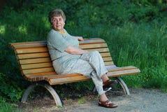 Signora anziana sul banco di sosta Fotografia Stock Libera da Diritti