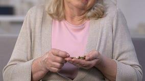 Signora anziana triste che conta le monete, ultimi soldi per vivere, povertà di pensionamento video d archivio