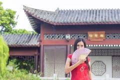 Signora asiatica che indossa cheongsam rosso in giardino, tenente un fan rosa di colore in sua mano Immagini Stock Libere da Diritti