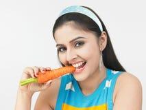 Signora asiatica che mangia una carota immagini stock libere da diritti