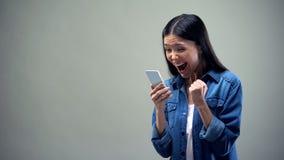 Signora asiatica che tiene smartphone, francamente rallegrandosi, tariffe favorevoli per le chiamate fotografia stock libera da diritti