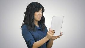 Signora asiatica di affari che chiacchiera facendo uso di una compressa su fondo bianco archivi video