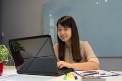 Signora asiatica sorridente dell'ufficio in posto di lavoro immagine stock libera da diritti