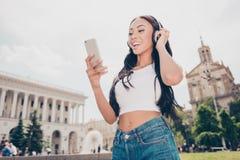 Signora attraente con pelle bronzea è in città soleggiata sulla passeggiata, dentro fotografia stock libera da diritti