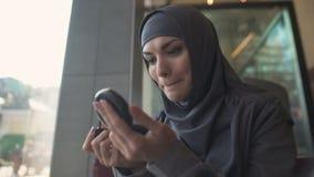 Signora attraente nel hijab tradizionale che applica il balsamo di labbro in caffè che sorride in specchio video d archivio