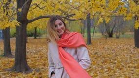 Signora In Beige Coat e sciarpa arancio che stanno indietro e prende un giro intorno a HD video d archivio