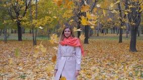 Signora In Beige Coat e sciarpa arancio gira intorno e getta Autumn Yellow Leaves archivi video