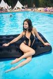 Signora in bikini nero che si siede su un materasso gonfiabile nella piscina e nel distogliere lo sguardo Priorità bassa vaga fotografia stock
