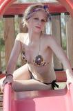 Signora bionda con il bikini d'uso dell'ente esile ed atletico divertendosi accanto ad un parco di divertimento fotografia stock libera da diritti