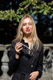 Signora bionda di fascino che porta cappotto nero e vestito che posano nei raggi o immagini stock