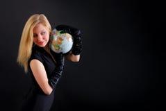 Signora bionda graziosa con il globo su fondo nero immagine stock