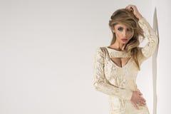 Signora bionda sexy in vestito dall'oro immagine stock