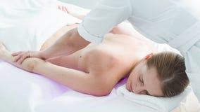 Signora calma che gode del massaggio del corpo alla stazione termale video d archivio