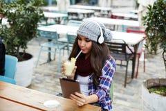 Signora in cappello divertente del volume che si siede sul caffè e sul cocktail bevente della banana Fotografia Stock Libera da Diritti