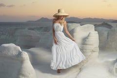 Signora in cappello in un paesaggio insolito immagini stock