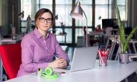 Signora carismatica di affari in abbigliamento casuale che si siede alla Tabella dell'ufficio Fotografie Stock