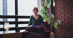 Signora carismatica la rende ad esercizi di un equilibrio yoga di pratica di mattina a casa sul sofà, indossante un comodo archivi video