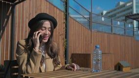 Signora castana allegra sta parlando dal telefono cellulare, sedentesi nel parco nel giorno soleggiato archivi video
