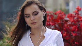 Signora castana ascolta la musica mentre si siede nel ristorante prima dei fiori rossi video d archivio
