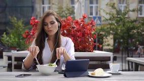 Signora castana ascolta la musica mentre si siede nel ristorante prima dei fiori rossi archivi video